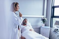 Doctor taking decision for treatment on hospitalised man. Physician in hospital room looking at patient monitoring device with sick men lying in bed. Doctor Stock Photography