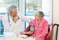 Doctor taking an elderly womans blood pressure. Stock Image