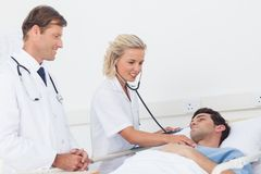 Doctor taking the heartbeat of her patient Stock Photos