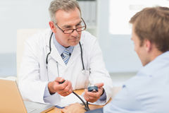 Doctor taking his patients blood pressure Stock Photos