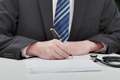 Doctor taking notes. Closeup of a doctor in suit taking notes Royalty Free Stock Photos