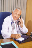 Doctor taking notes during phone call Royalty Free Stock Photography