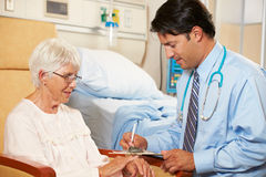 Doctor Taking Notes From Senior Female Patient Seated In Chair. By Hospital Bed Royalty Free Stock Images