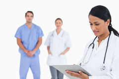 Doctor taking notes with staff behind her Royalty Free Stock Photography