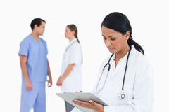 Doctor taking notes with talking staff members Royalty Free Stock Images