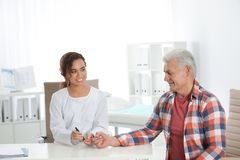 Doctor taking patient`s blood sample with lancet pen in hospital. Diabetes control royalty free stock photo