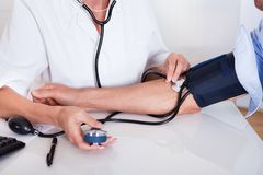 Doctor taking a patients blood pressure Stock Photo