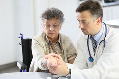Doctor taking the pulse of an elderly woman Royalty Free Stock Photo