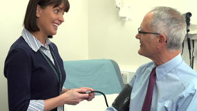 Doctor Taking Senior Male Patient's Blood Pressure stock video footage