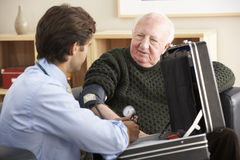 Doctor taking senior man's blood pressure at home Stock Images