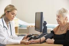 Doctor taking senior woman's blood pressure Stock Photo