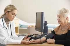 Doctor taking senior woman's blood pressure Stock Photo