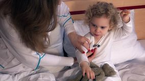 Doctor taking temperature of a little child girl in examination room stock footage