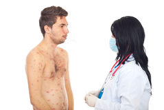 Doctor taking temperature to sick male. Doctor taking temperature to a sick male with chickenpox isolated on white background Stock Photo