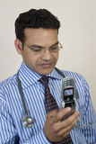 Doctor taking urgent call. Young Indian Doctor taking urgent call on his mobile phone Stock Photo