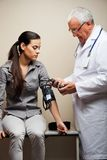 Doctor Taking Woman's Blood Pressure Royalty Free Stock Images