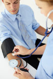 Doctor taking young man's blood pressure Stock Photography