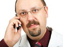 Doctor talking on a cell phone Stock Images