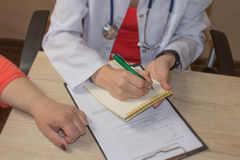 Doctor is talking with female patient and making notes while sit Stock Photo