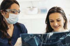 Doctor talking with her patient and teaching a radiograph. Royalty Free Stock Images
