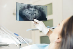 Doctor talking with her patient and teaching a radiograph. Royalty Free Stock Photos