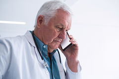 Doctor talking on his mobile phone in the passageway. At hospital Stock Photography