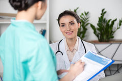 Doctor talking with internist writing in clipboard with diagnosis in clinic Stock Photography