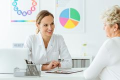 Doctor talking about losing weight. Young female doctor talking to her patient about losing weight and healthy diet Stock Photo