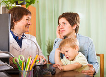 Doctor talking with mother of baby Stock Photos