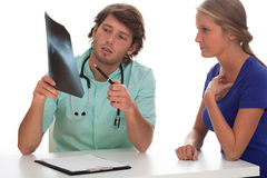 Doctor showing x-ray photo to his patient. Stock Photos