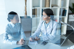 Doctor talking with patient during medical consultation at office. Young doctor talking with patient during medical consultation at office Stock Photo