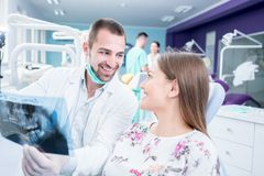 Doctor talking with patient and showing a radiograph in stomatology clinic. Dentist concept. stock photography