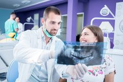 Doctor talking with patient and showing a radiograph in stomatology clinic. Dentist concept. royalty free stock image