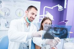 Doctor talking with patient and showing a radiograph in stomatology clinic. Dentist concept. royalty free stock photos