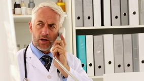 Doctor talking on the phone at his desk stock video footage