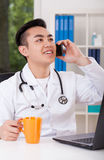 Doctor talking on the phone Stock Images