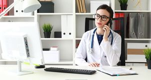 Doctor talking on phone and looking at monitor. Doctor talking on phone and looking at monitor stock video footage