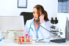 Doctor talking on phone and looking in monitor Stock Photos
