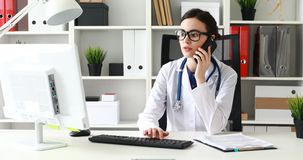 Doctor is talking on phone and looking at monitor.  stock footage