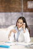 Doctor talking on phone in office. Female doctor sitting at desk in doctor's room talking on phone, smiling. Copyspace above head Royalty Free Stock Images