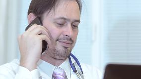 Doctor talking on the phone in the office. stock video