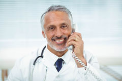 Doctor talking on phone. Portrait of doctor talking on phone in clinic Royalty Free Stock Photo