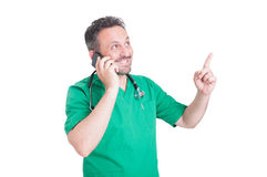 Doctor talking on the phone and smiling. While looking and pointing finger up Stock Image