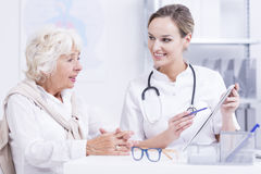 Doctor talking with the senior woman. Smiled doctor with the stethoscope talking with the senior woman stock photos