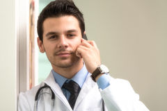 Doctor Talking On Telephone In Office. Young Doctor Talking On The Phone Stock Photography