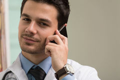 Doctor Talking On Telephone In Office. Young Doctor Talking On The Phone Royalty Free Stock Photos