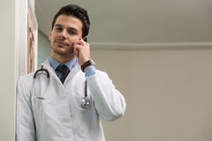 Doctor Talking On Telephone In Office. Young Doctor Talking On The Phone Stock Images