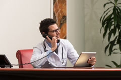 Doctor Talking On Telephone In Office Royalty Free Stock Photography