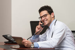 Doctor Talking On Telephone In Office Stock Photos