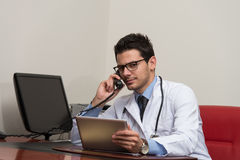 Doctor Talking On Telephone And Using Computer Stock Photos